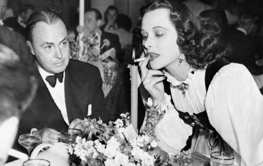 SZT2999340 Gene Markey and Hedy Lamarr, 1939 (b/w photo); (add.info.: Los Angeles, California, United States of America Hedy Lamarr with her husband, the writer Gene Markey, on a party in Hollywood, given by Basil Rathbone and his wife. The actress lights a cigarette on a candle. Gene Markey und Hedy Lamarr, 1939); © SZ Photo / Scherl; PERMISSION REQUIRED FOR NON EDITORIAL USAGE;  out of copyright  PLEASE NOTE: Bridgeman Images works with the owner of this image to clear permission. If you wish to reproduce this image, please inform us so we can clear permission for you.