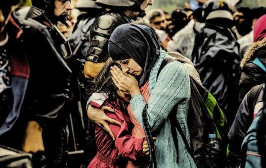 Tovarnik, Croacia: una mujer consuela a su hija que llora en medio de un tumulto en la estación de tren, donde miles de refugiados esperan subirse a un tren o a un autobús que les lleve a otro destino en la UE.