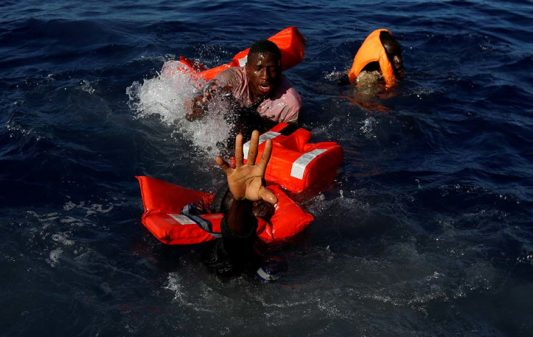 """Migrants try to stay afloat after falling off their rubber dinghy during a rescue operation by the Malta-based NGO Migrant Offshore Aid Station (MOAS) ship in the central Mediterranean in international waters some 15 nautical miles off the coast of Zawiya in Libya, April 14, 2017. All 134 sub-Saharan migrants survived and were rescued by MOAS.  REUTERS/Darrin Zammit Lupi     TPX IMAGES OF THE DAY     SEARCH """"MOAS RESCUE"""" FOR THIS STORY. SEARCH """"WIDER IMAGE"""" FOR ALL STORIES. - RC1BB6D33F80"""